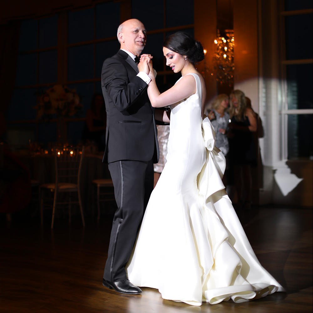 Father and bride dancing in a spotlight